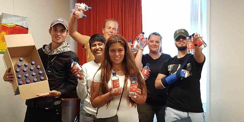 Achterban jongeren delen flesjes water uit aan hun leeftijdsgenoten