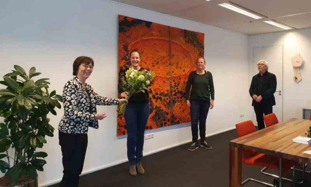 Wethouder Bert van Alphen ontvangt bloemen voor actieplan jongeren